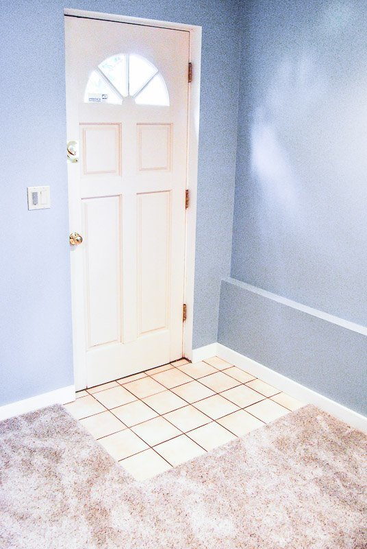 The carpet over tile stopped at the door to allow it to open freely.