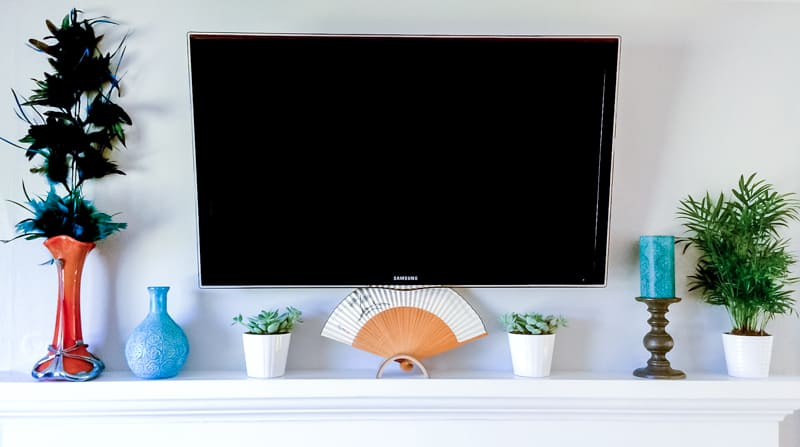 wall mounted TV over fireplace with decor hiding the outlet