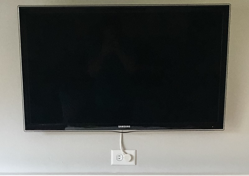 wall mounted TV with Apple TV mount hidden behind