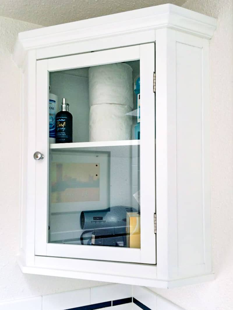 small bathroom corner cabinet with glass door installed on the wall