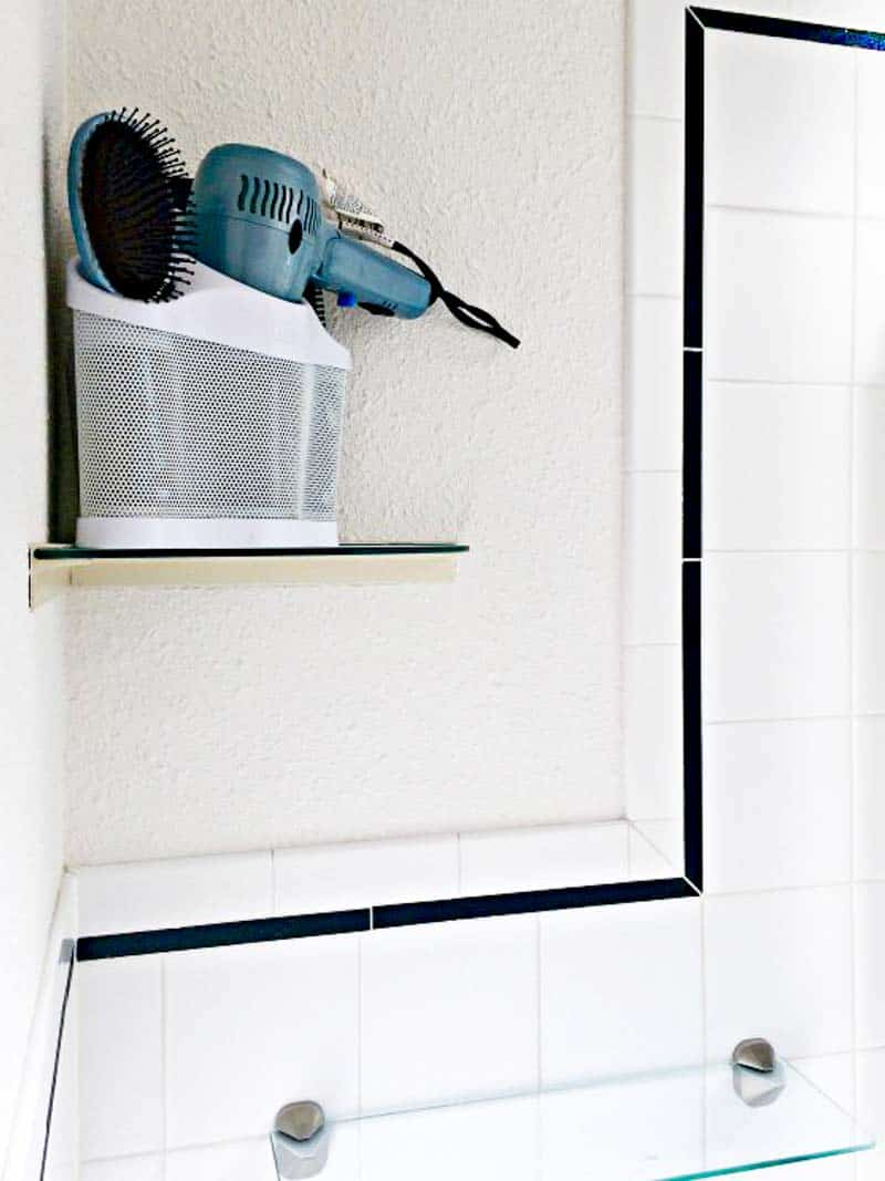 small bathroom corner shelf with hair dryer and brushes