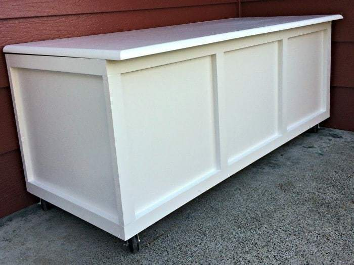 The door hinges in the back of this DIY storage bench raise the lid slightly, which allows water to run off instead of pooling on top