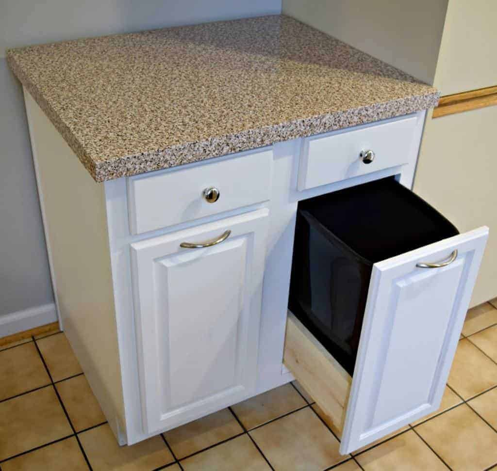 kitchen cabinet with pull out trash can and contact paper countertop