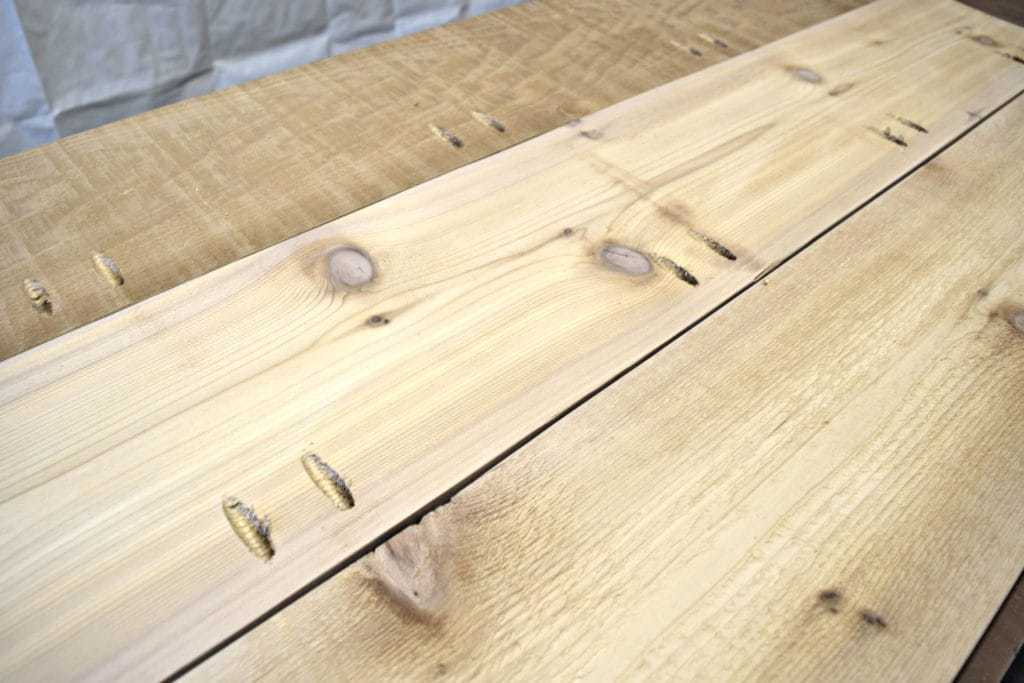 Attach the cedar boards of the outdoor storage bench lid together with pocket hole screws - www.thehandymansdaughter.com