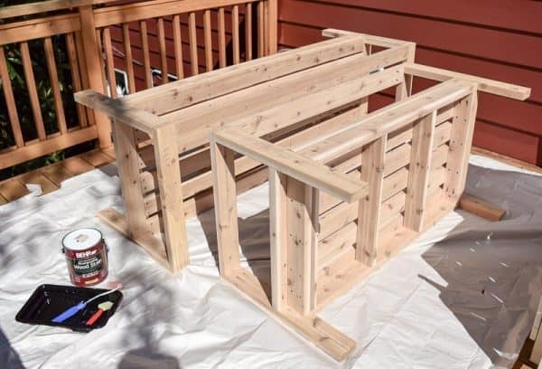 applying wood stain to DIY outdoor loveseat and sofa