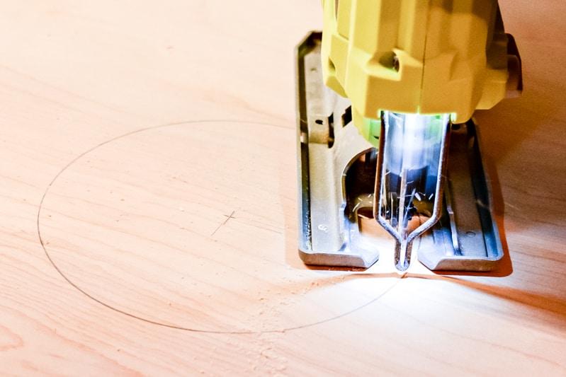 cutting a hole for the cornhole board with a jigsaw