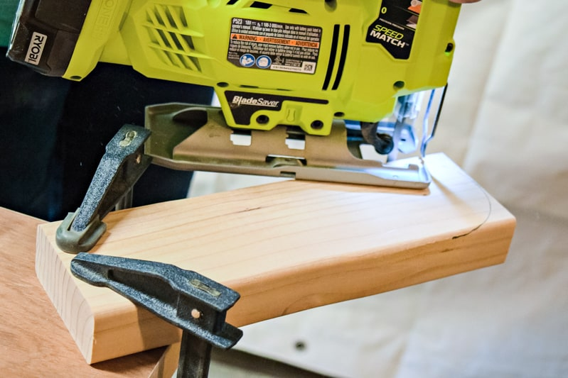 cutting a curve on the ends of the DIY cornhole board leg with a jigsaw