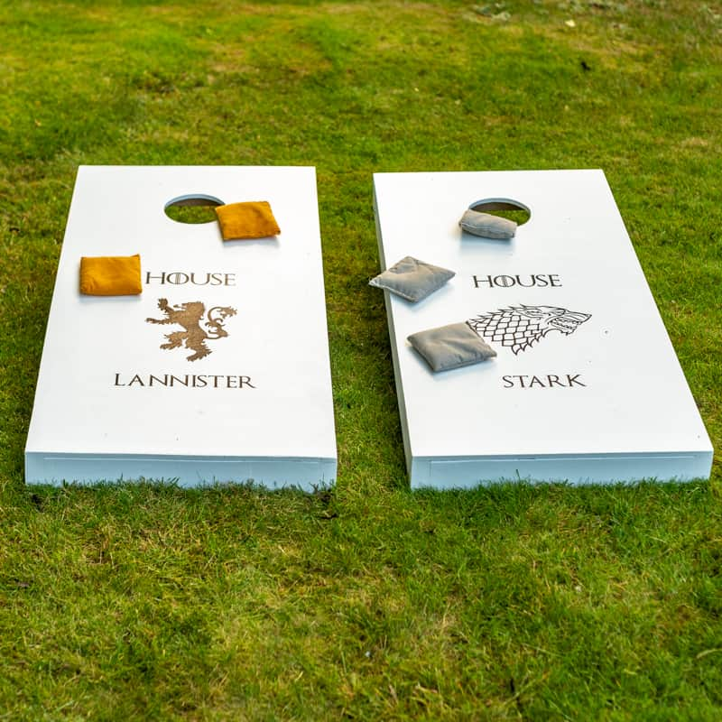 Game of Thrones themed DIY cornhole boards on grassy lawn