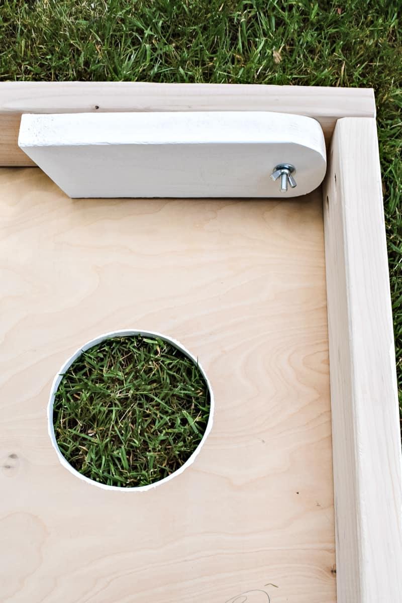 collapsible leg of DIY cornhole board inside frame with circular hole