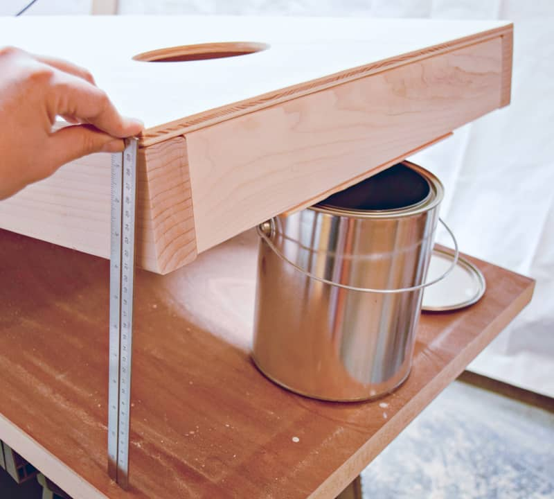 DIY cornhole board end propped up on paint can with ruler measuring 12 inches
