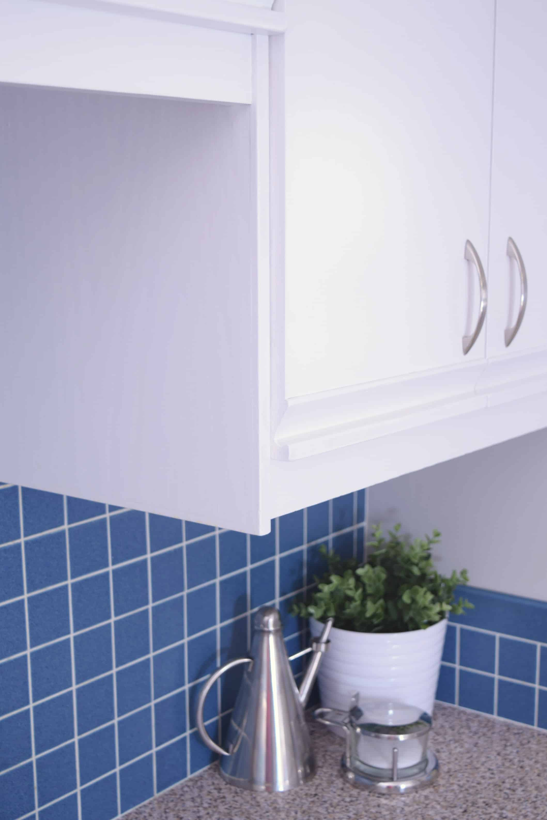 white painted kitchen cabinets with blue backsplash