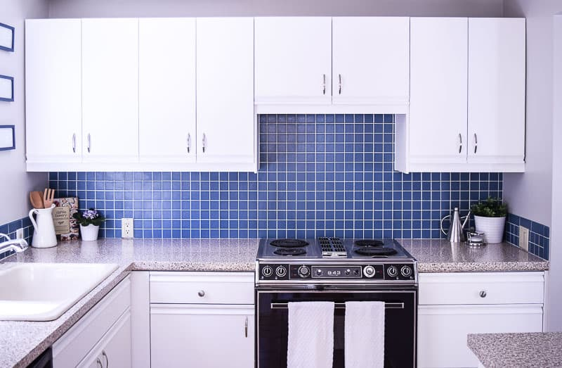 full view of painted kitchen cabinets with blue backsplash