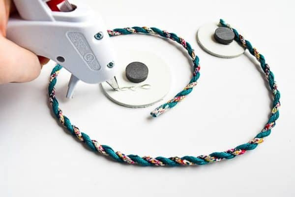length of cord being glued to two circles with magnets