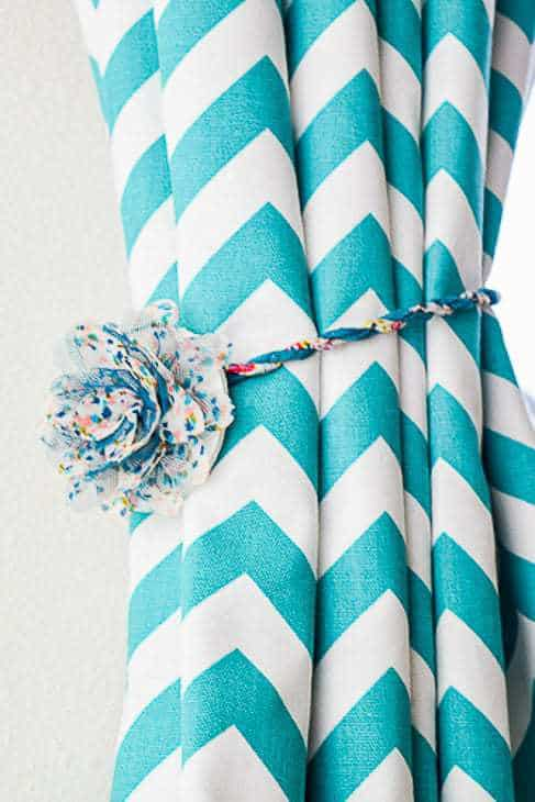 turquoise and white chevron curtain held open with a magnetic curtain tie back with a faux flower decoration