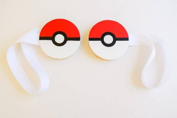 two magnetic curtain tie backs with pokeballs painted on white wooden circles