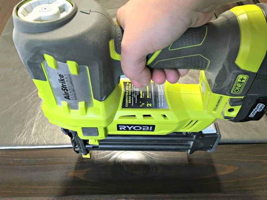 Attach 1 x 4 boards to the edge of your leather headboard. The Ryobi Airstrike brad nailer made this step easy! - The Handyman's Daughter