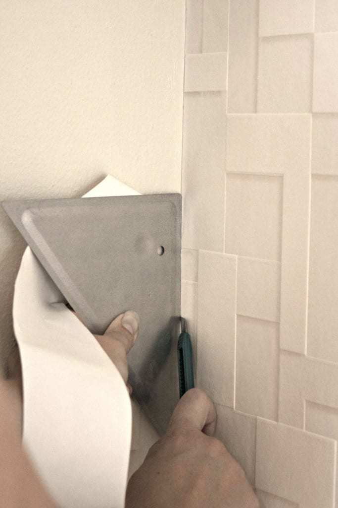Use a straight edge to trim excess textured wallpaper at the corners for a perfect fit! - The Handyman's Daughter