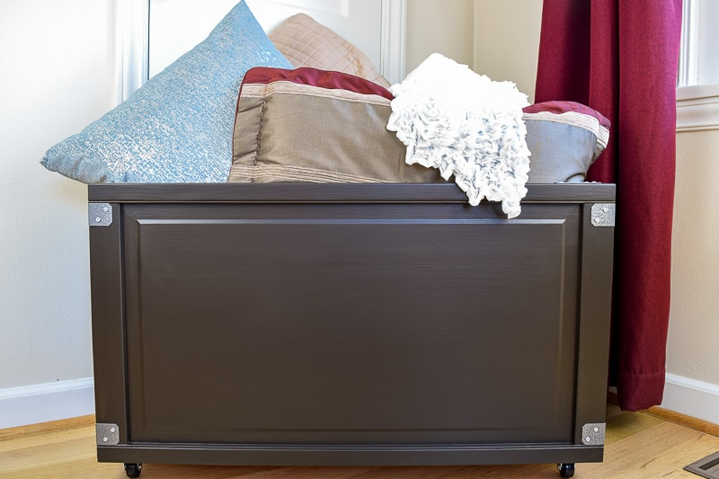 rolling blanket storage box filled with blankets and pillows