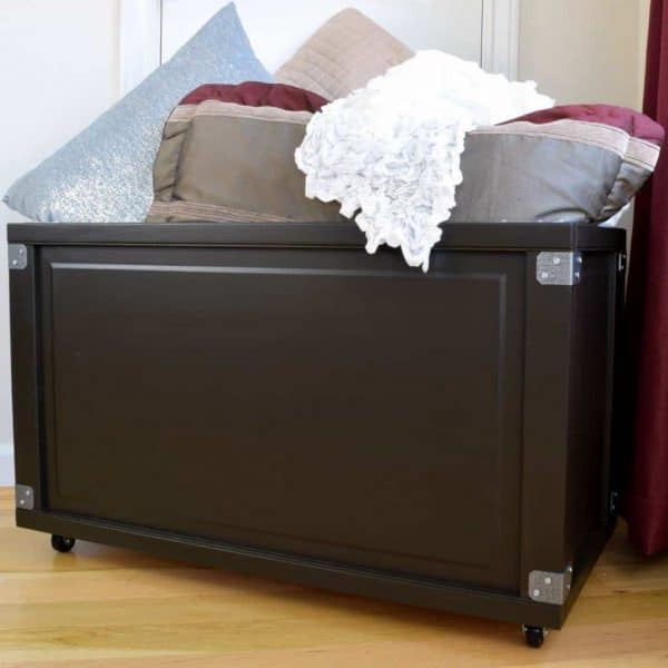blanket box with pillows stacked on top