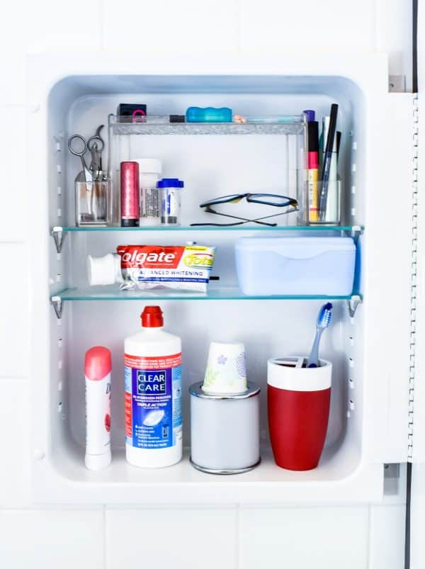 painted metal medicine cabinet with toiletries inside