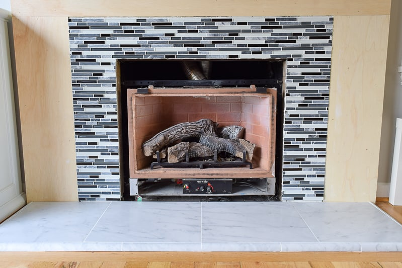 stone and glass tile fireplace over original brick fireplace