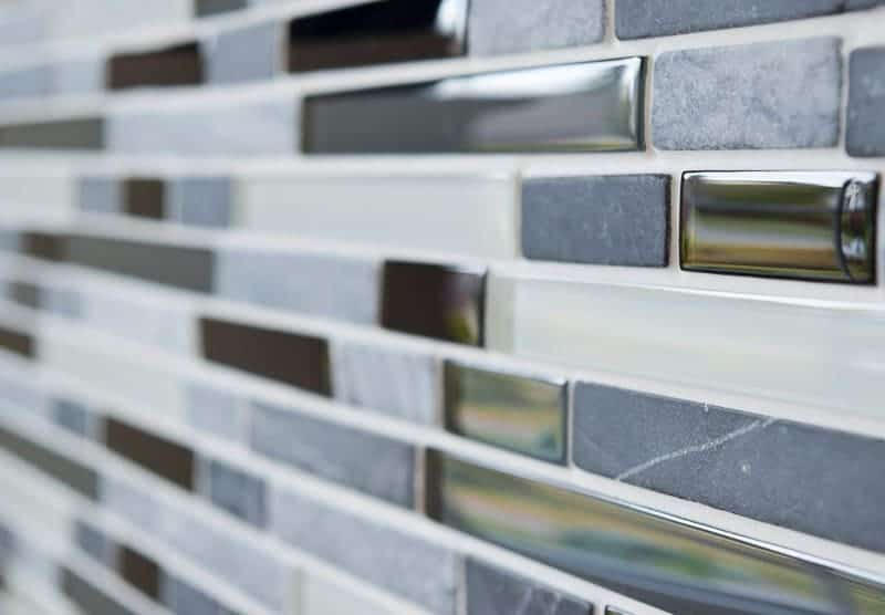 Sanded grout can scratch glass tiles. I used unsanded grout for my fireplace tile.