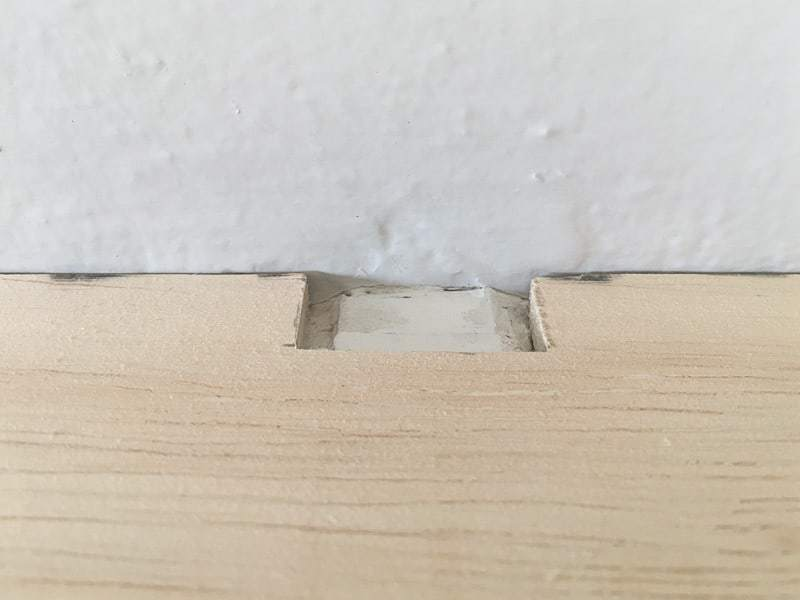 "Our mantel had an ugly bulge on the top from the bracket holding it in place. Before attaching the fireplace trim, I covered up the bump with 1/4"" plywood."
