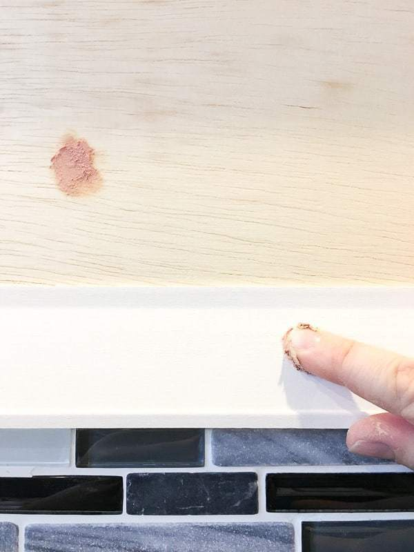 Wood filler hides any nail holes in the fireplace trim.