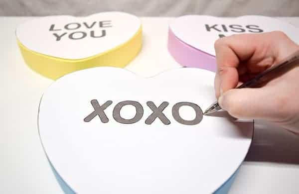 Trace the outline of the letters onto the giant conversation hearts with a ballpoint pen.