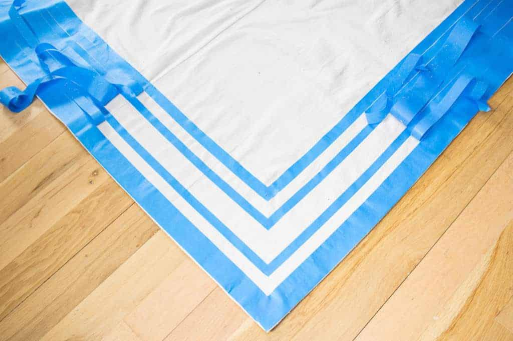 Use painter's tape to create the grain sack stripes on your drop cloth rug.