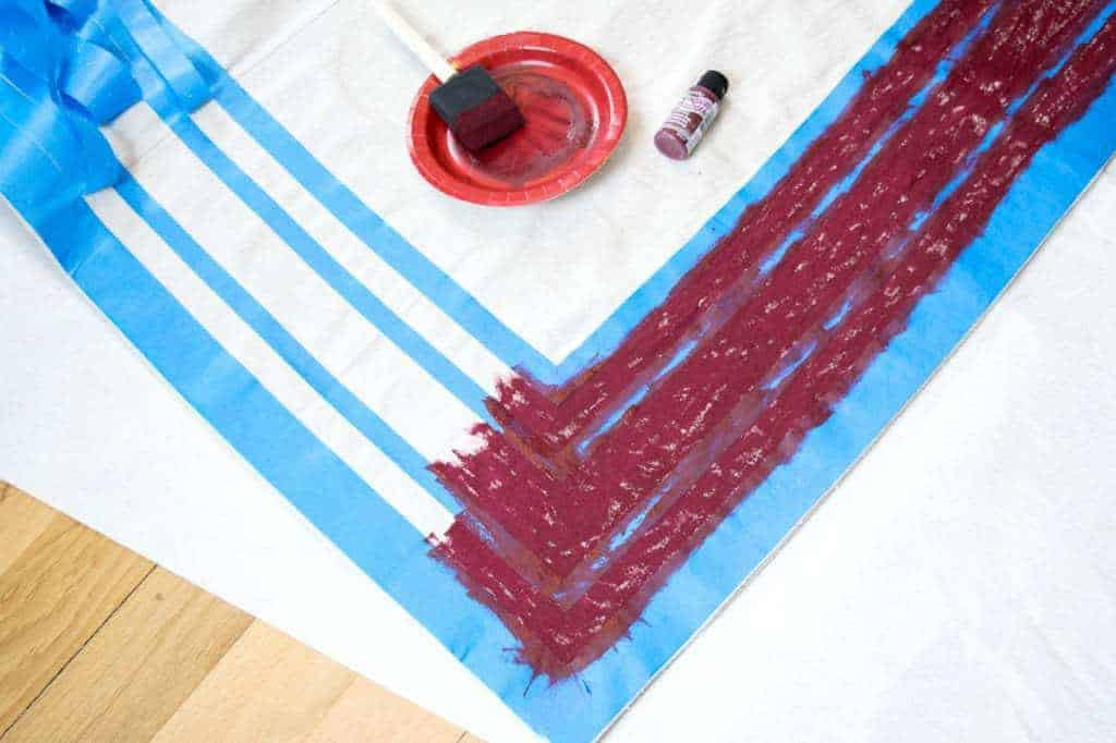 Use a foam brush to dab fabric paint onto the drop cloth in between the painter's tape lines.