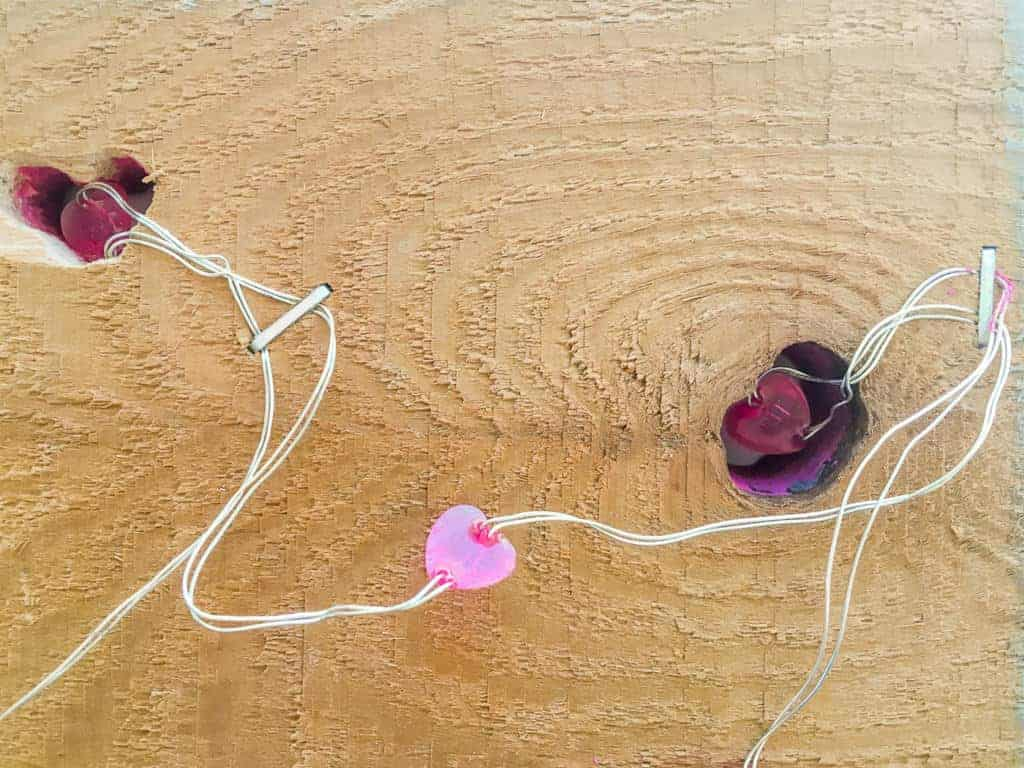 Staple the heart light wires to the back of the Valentine's Day sign to keep them in position.