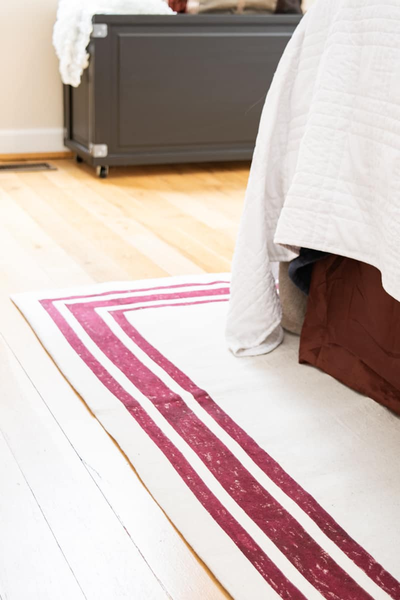 DIY rug with red stripes under bed with red bed skirt and blanket box in the background