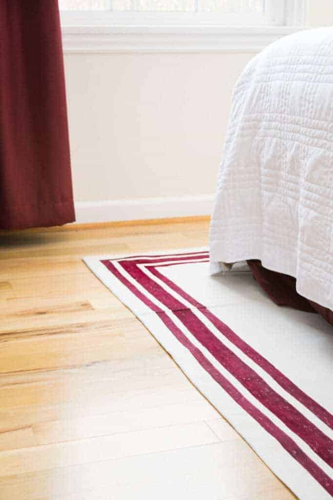 It's easy to make your own rug with just a drop cloth and fabric paint! Customize your rug to fit your decor. | drop cloth rug | how to make a rug | striped rug