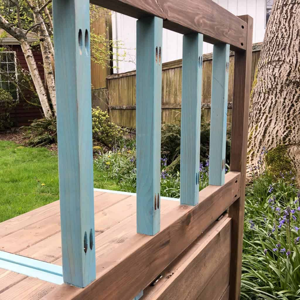 The back of this DIY storage bench is decorated with 2 x 2 slats stained with Vintage Aqua.