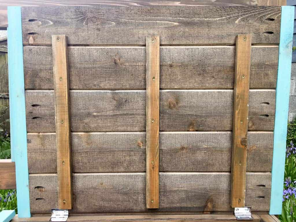 The underside of the lid of this DIY storage bench has additional structural support underneath, and pocket holes hold the finishing pieces to the ends.