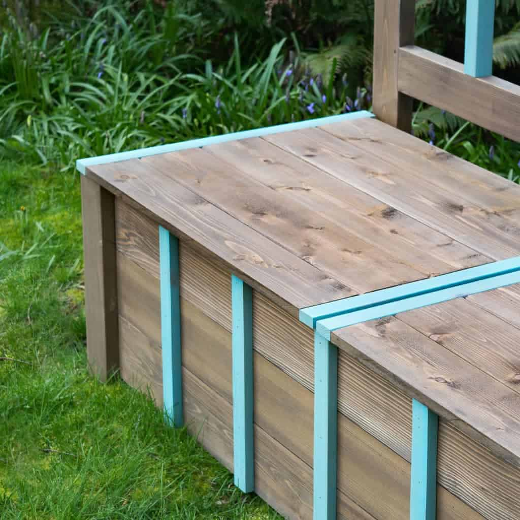My DIY storage bench gives a nice pop of color and lots of storage to this dark corner of the garden.