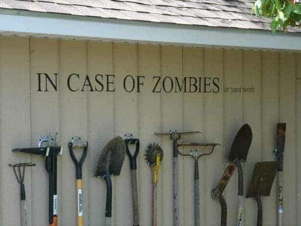 "garden tool storage on wall with text reading ""in case of zombies or yard work"""