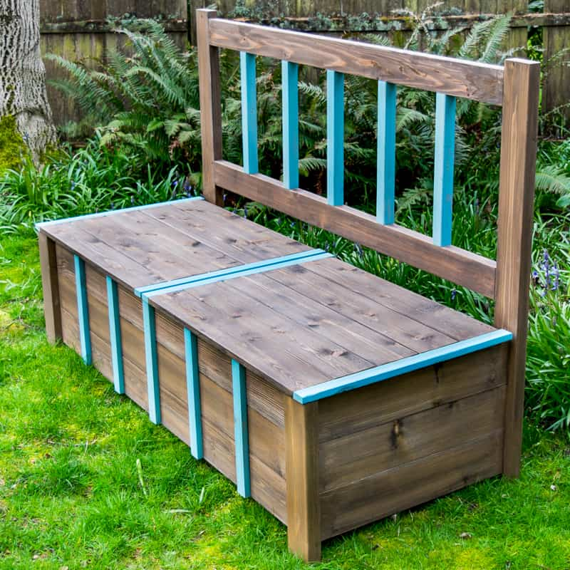 DIY outdoor storage bench on grass with ferns in background