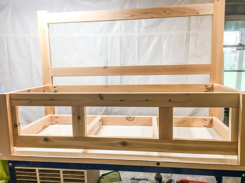attaching the front legs to the frame of the outdoor storage bench