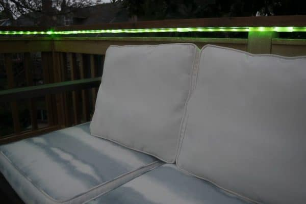 green outdoor rope lights under deck railing next to outdoor loveseat