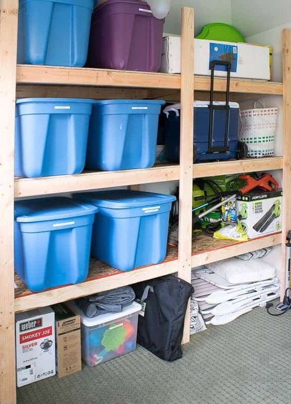 plastic bins and outdoor equipment stored on shed shelving