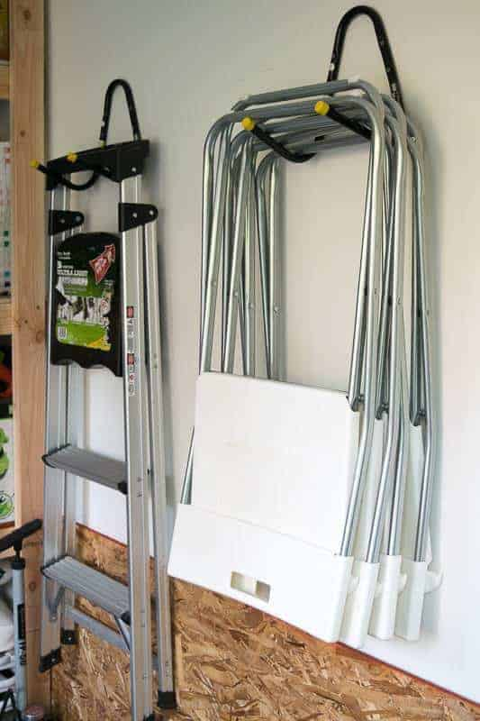 ladder and folding chairs hung on the wall next to shed shelving