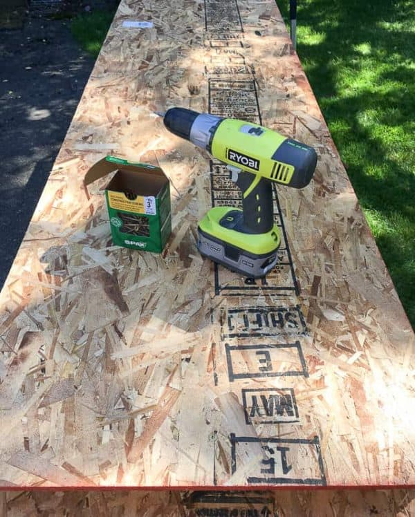 """Attach the top sheet of OSB to the frame of the storage shelves with 3"""" screws."""