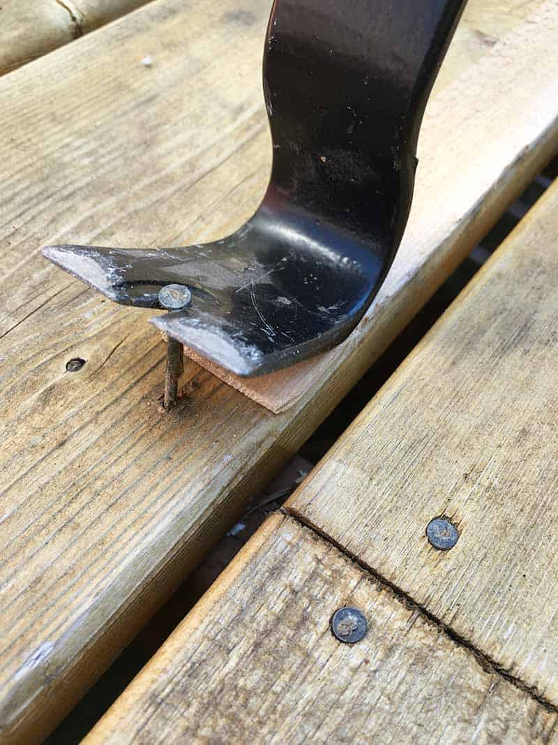 pry bar end of nail puller used to pull out raised nail from deck