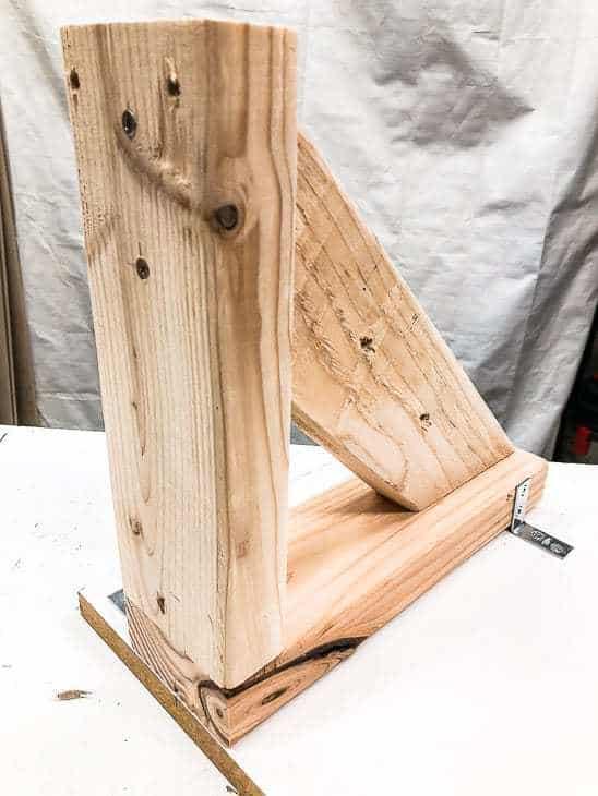 Attach the garden tool storage rack brackets to the shelf.