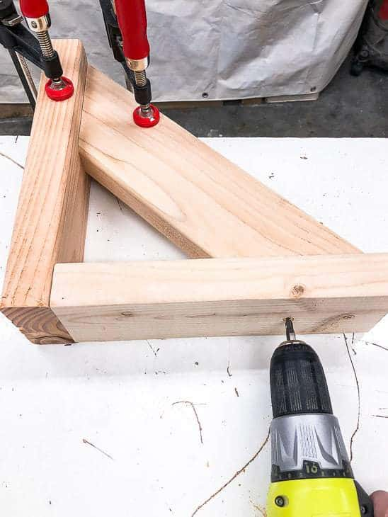 Attach the angled pieces to the L shaped bracket of the garden tool storage rack.