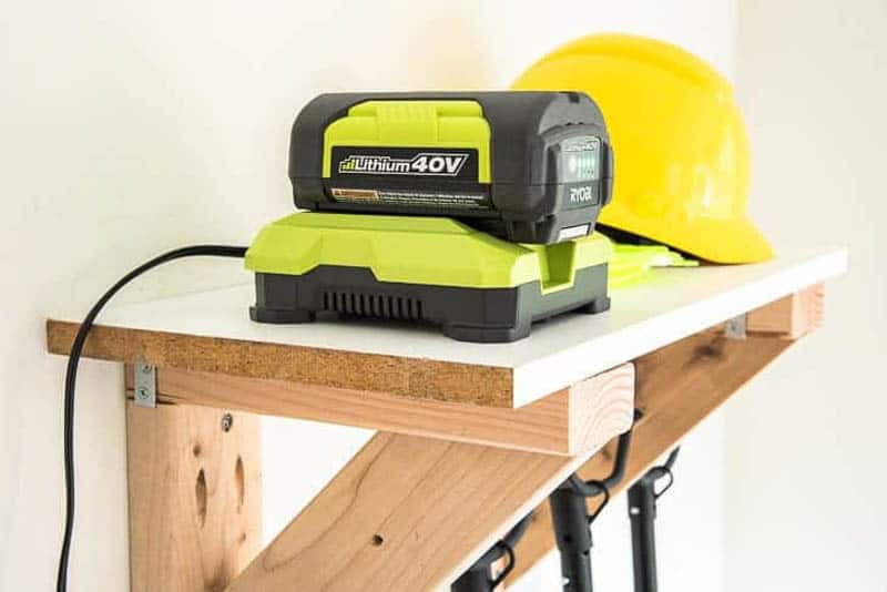 battery charger and hard hat sitting on shelf of garden tool storage rack
