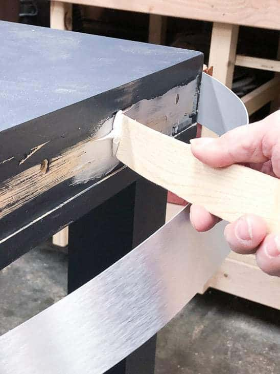 Use construction adhesive to attach the metal banding to the desk.