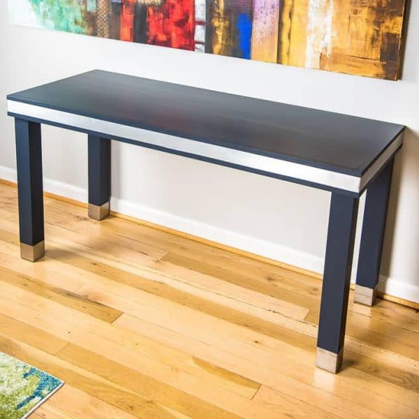 The navy blue paint contrasts beautifully with the brushed aluminum accents of this wood and metal desk.